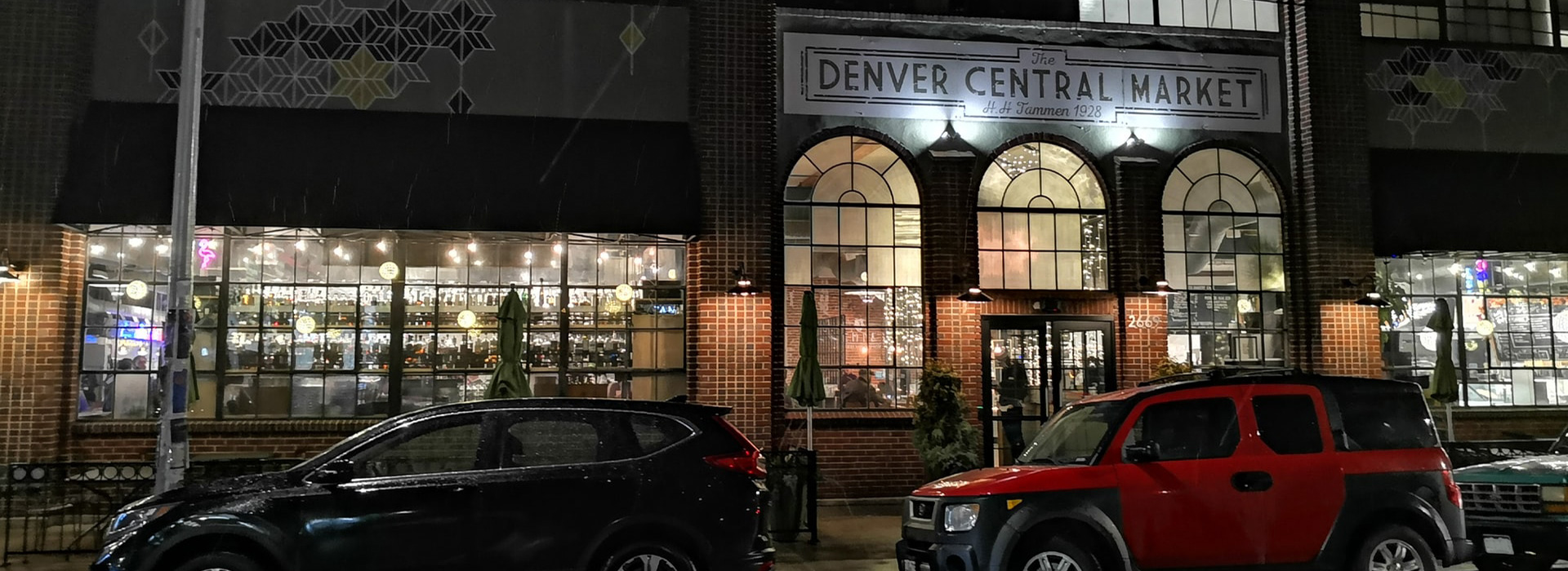 cars parked in front of Denver Central Market at night